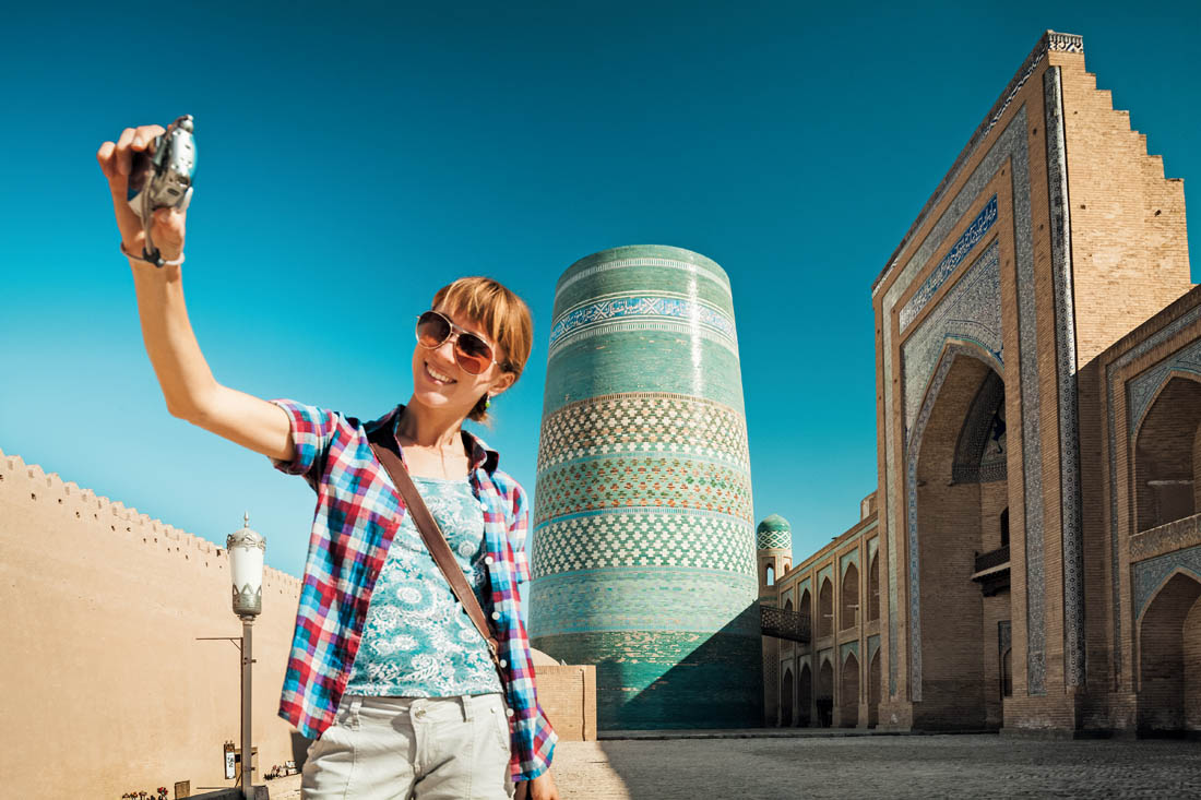Young lady taking a selfie with the oriental buildings in Itchan Kala ancient town on the background. Khiva, Uzbekistan